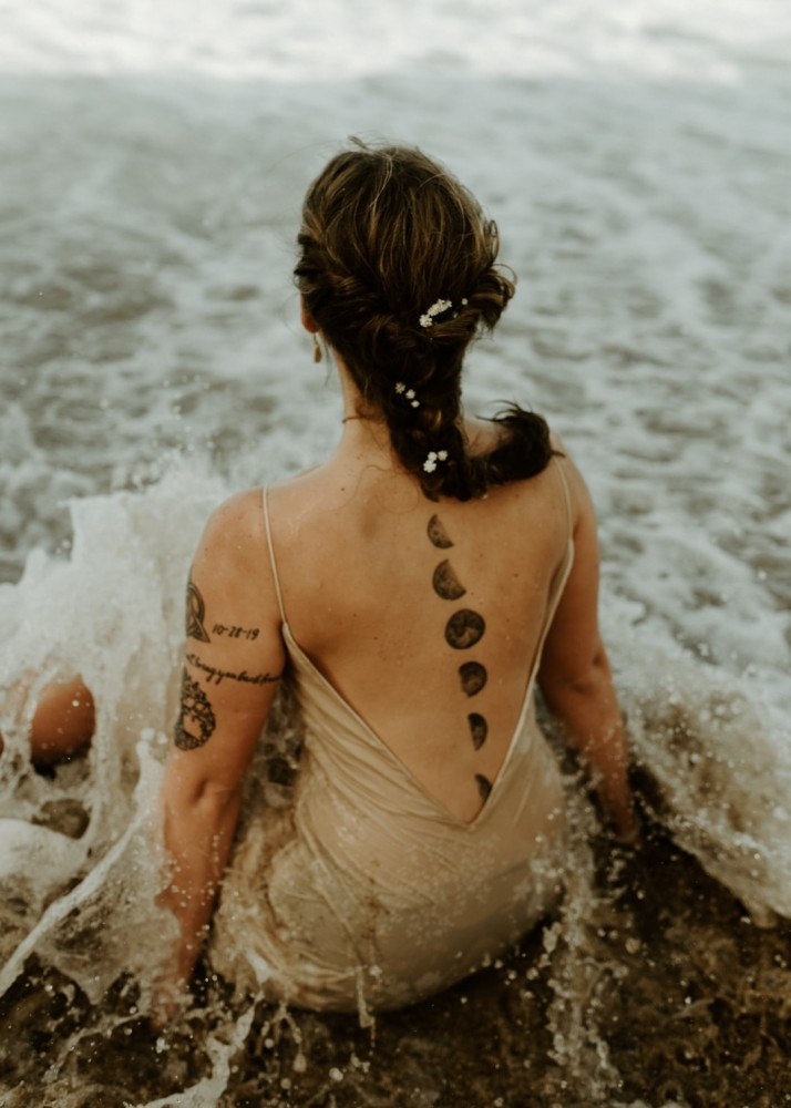 Witch with moon tattoos sitting in the waves on a beach