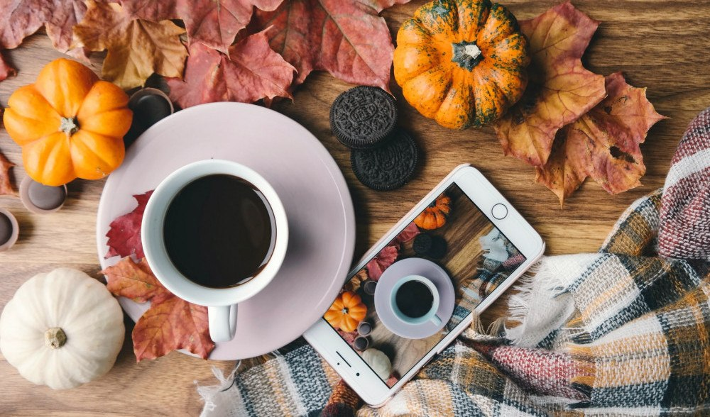 Fall vibes with small pumpkins, a warm drink, and autumn leaves